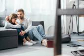 schöner Mann beruhigt traurige Frau in beraubter Wohnung