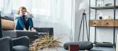 Panoramaaufnahme einer attraktiven und traurigen Frau, die auf einem Sofa in einer ausgeraubten Wohnung sitzt