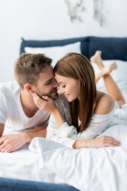 attractive and smiling woman hugging handsome man in apartment
