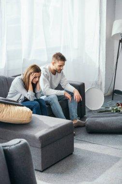 sad woman and handsome man sitting on sofa in robbed apartment