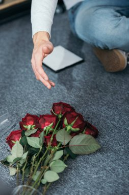 cropped view of man and flowers on floor in robbed apartment