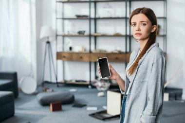 sad woman holding smartphone with blank screen in robbed apartment