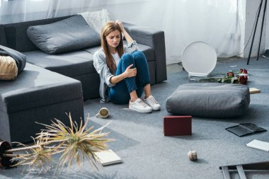 attractive and sad woman sitting on floor in robbed apartment