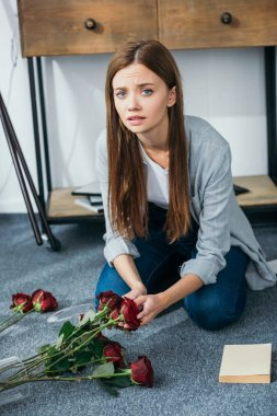 attractive and sad woman holding flowers in robbed apartment