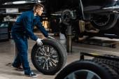 fiatal szerelő gazdaság autó kerék közelében emelt autó műhelyben