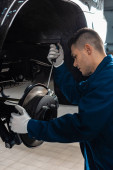 Photo attentive mechanic adjusting brake caliper with screw driver