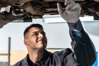 concentrated mechanic examining raised car in workshop