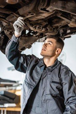 attentive mechanic examining raised car in workshop