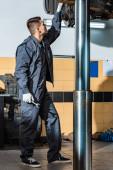mladý mechanik kontroluje zdvižené auto v dílně