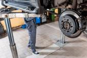selektivní zaměření smontovaných kotoučových brzd v blízkosti mladého mechanika zkoumajícího zdvižený vůz