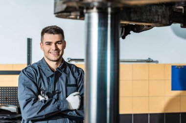 smiling mechanic looking at camera while standing near raised car in workshop