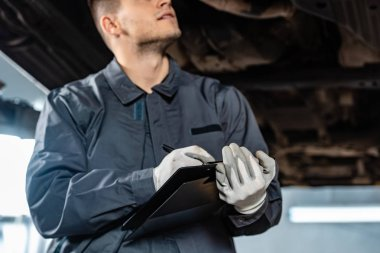 cropped view of mechanic writing on clipboard while standing under raised car