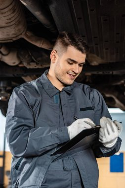 smiling mechanic writing on clipboard while standing under raised car
