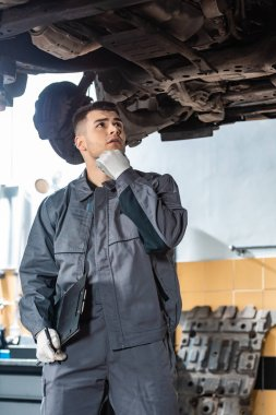 thoughtful mechanic holding hand near face while looking at car bottom