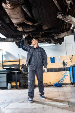 young mechanic inspecting bottom of raised car in workshop