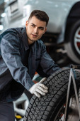 Photo young confident mechanic looking away near car wheel in workshop