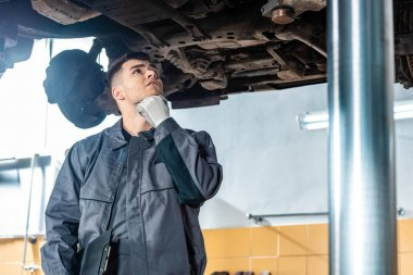 thoughtful mechanic inspecting car raised on car lift in workshop