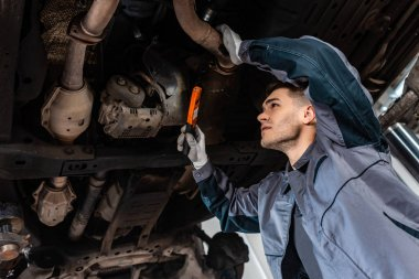 attentive mechanic inspecting bottom of car with flashlight