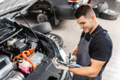 smiling mechanic writing on clipboard while inspecting car engine compartment
