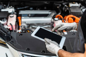 cropped view of mechanic using digital tablet near car engine compartment
