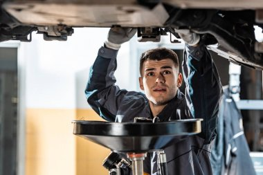 young mechanic looking at bottom of car near lube oil extractor