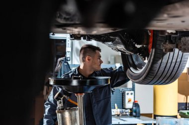 selective focus of mechanic standing under raised car near waste oil extractor