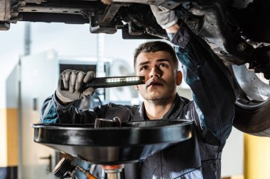 attentive mechanic inspecting car bottom with flashlight near waste oil extractor