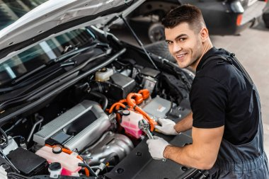 Handsome mechanic inspecting car engine compartment and smiling at camera stock vector