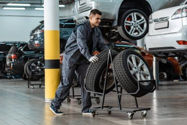 handsome, smiling mechanic taking new tire from stand near modern cars in workshop