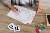 Ausgeschnittene Ansicht einer Frau, die ein Geburtshoroskop aus Steinen und Papieren mit Tierkreiszeichen auf dem Tisch zeichnet