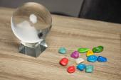 Kristallkugel und bunte Steine mit Sternzeichen auf Holztisch