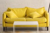 Žlutý gauč s polštáři a bílý konferenční stolek v obývacím pokoji