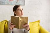 Figyelmes lány kezében könyv és nézte félre kanapén otthon