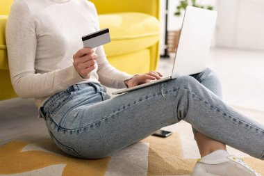 Cropped view of young woman holding credit card and using laptop on floor in living room stock vector