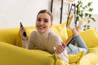 Kanepede yatarken elinde akıllı telefon ve kredi kartıyla gülümseyen kadın.
