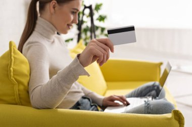 Selective focus of smiling girl showing credit card and using laptop on sofa stock vector