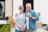 zralé muž držící klíče nového domu a objímající usměvavá žena