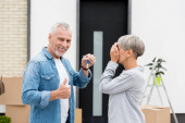Photo mature man holding keys of new house and showing like and woman obscuring face