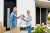 zralé muž dává klíče od nového domu k usmívající se ženě