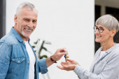 mature man giving keys of new house to smiling woman