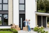 Fotografie Reifer Mann und lächelnde Frau tanzen und schauen einander in der Nähe des neuen Hauses an