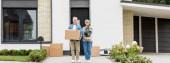 panoráma lövés érett férfi holding box és nő holding növény közelében új ház