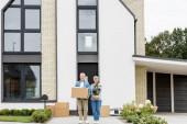 zralé muž držení box a žena drží rostlina v blízkosti nového domu