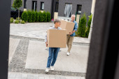 Photo mature man and smiling woman bringing boxes to new house