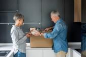 boční pohled na zralého muže a usměvavé ženy unpacking box v novém domě