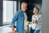 smiling man and mature woman holding cups in new house