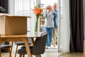 Photo selective focus of smiling man obscuring face of woman in new house