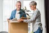 usmívající se muž a zralá žena vybalování box v novém domě
