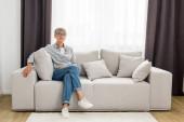 Reife Frau in Brille sitzt auf Sofa in neuem Haus