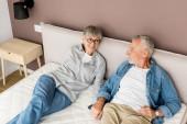 zralé muž a usmívající se žena drží ruce v posteli v novém domě